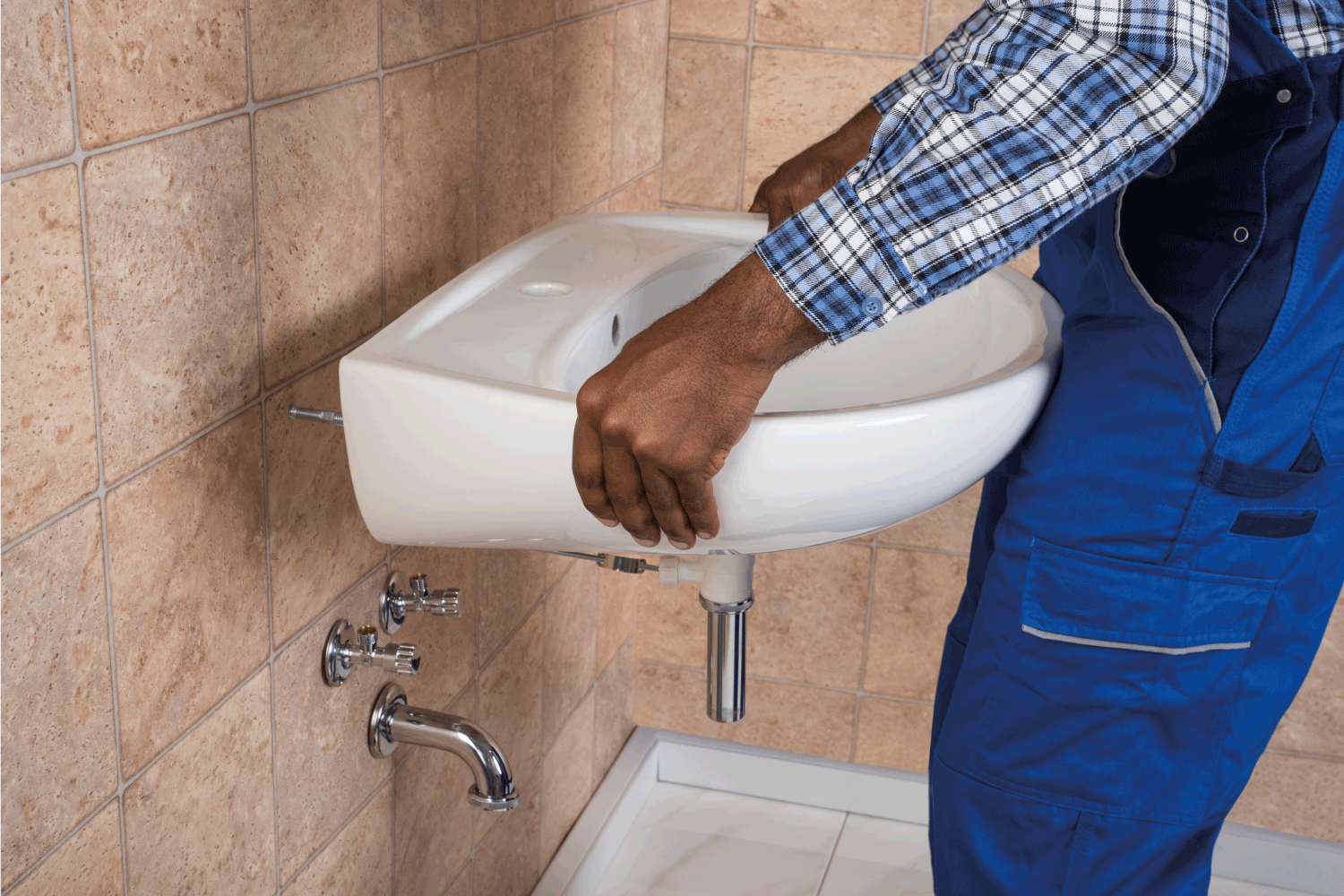 Close-up Of Young African Handyman Fixing Sink In Bathroom