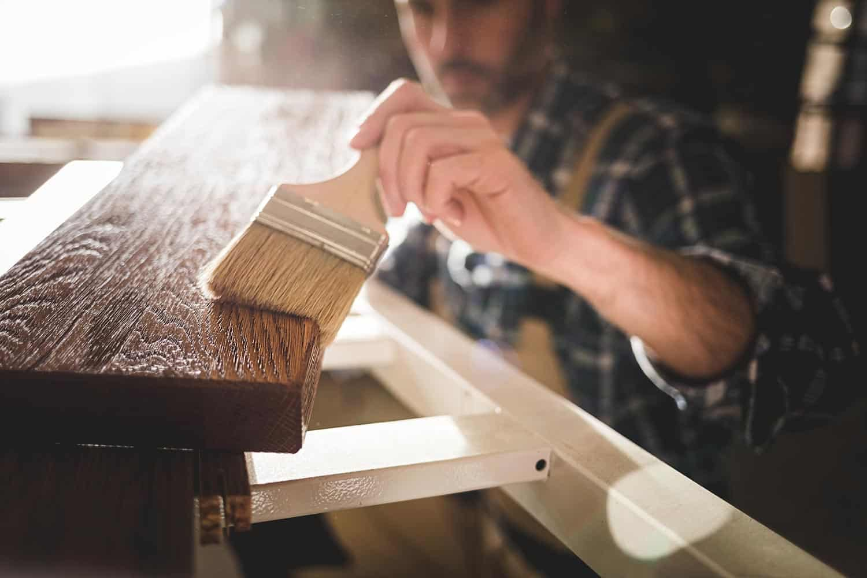 Carpenter using paintbrush applying paint or varnish on wooden board in carpentry workshop