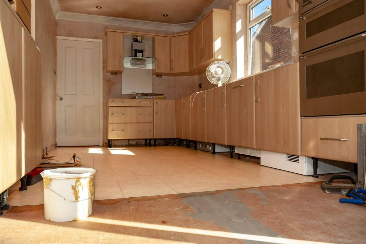 Interior of an unfinished kitchen with wooden cabinetry and unfinished cabinetry