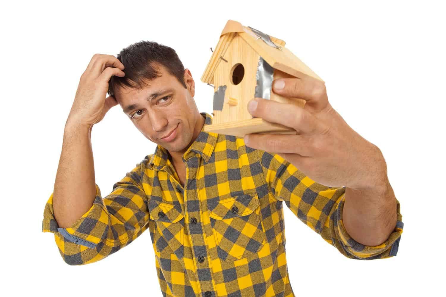 Man holds a birdhouse put together with bent nails and duct tape