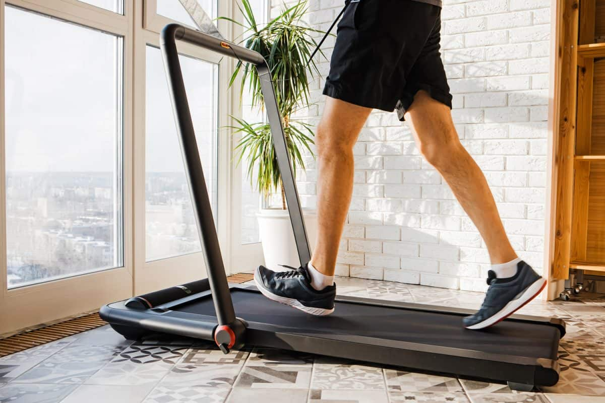 Man jogging on the modern compact treadmill at his home, close-up shot of feet in sneakers. Modern lifestyle, sport indoors.