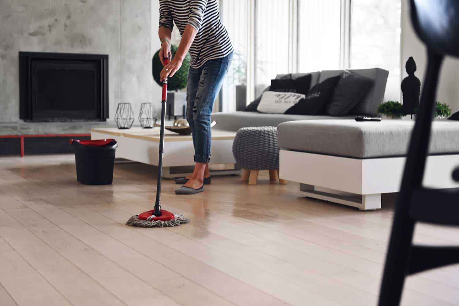 Mature woman cleaning floor while quarantined at home