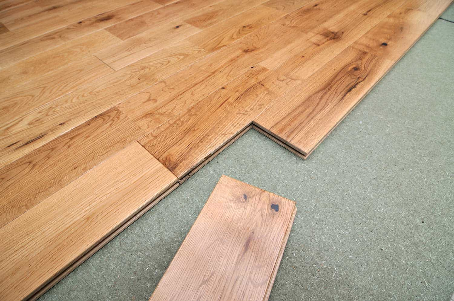 Partially laid oak floorboards, showing the insulation underneath