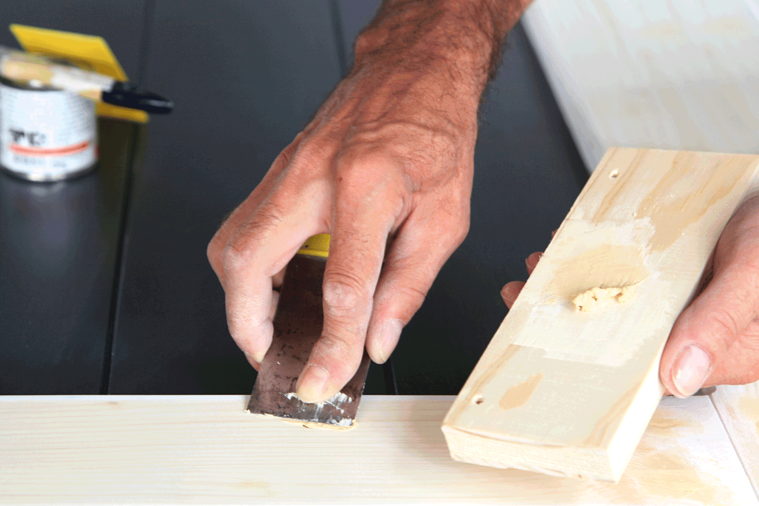 Preparation woodwork. Close-up details Putty knife in man's hand. DIY worker applying filler to the wood. Removing holes from a wood surface. Application of putty