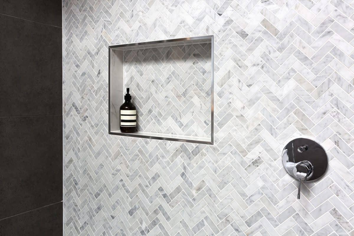 Shower shelf detail in wall of herringbone marble tiles in a luxury new home