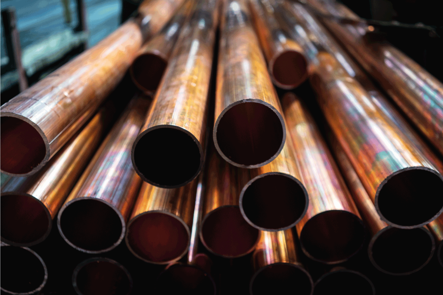 close up photo of stacked copper pipes