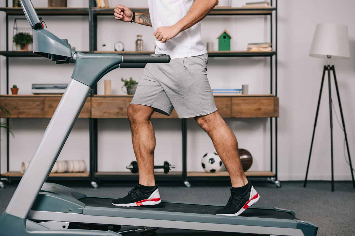 cropped view of muscular sportsman running on treadmill