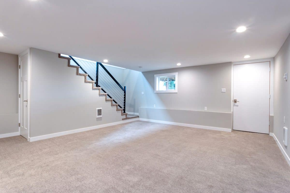 A carpeted empty basement with white painted walls, recessed lighting, and a white door