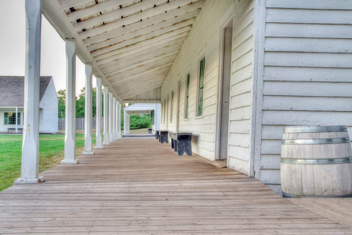 A long narrow wooden porch of a ranch style house