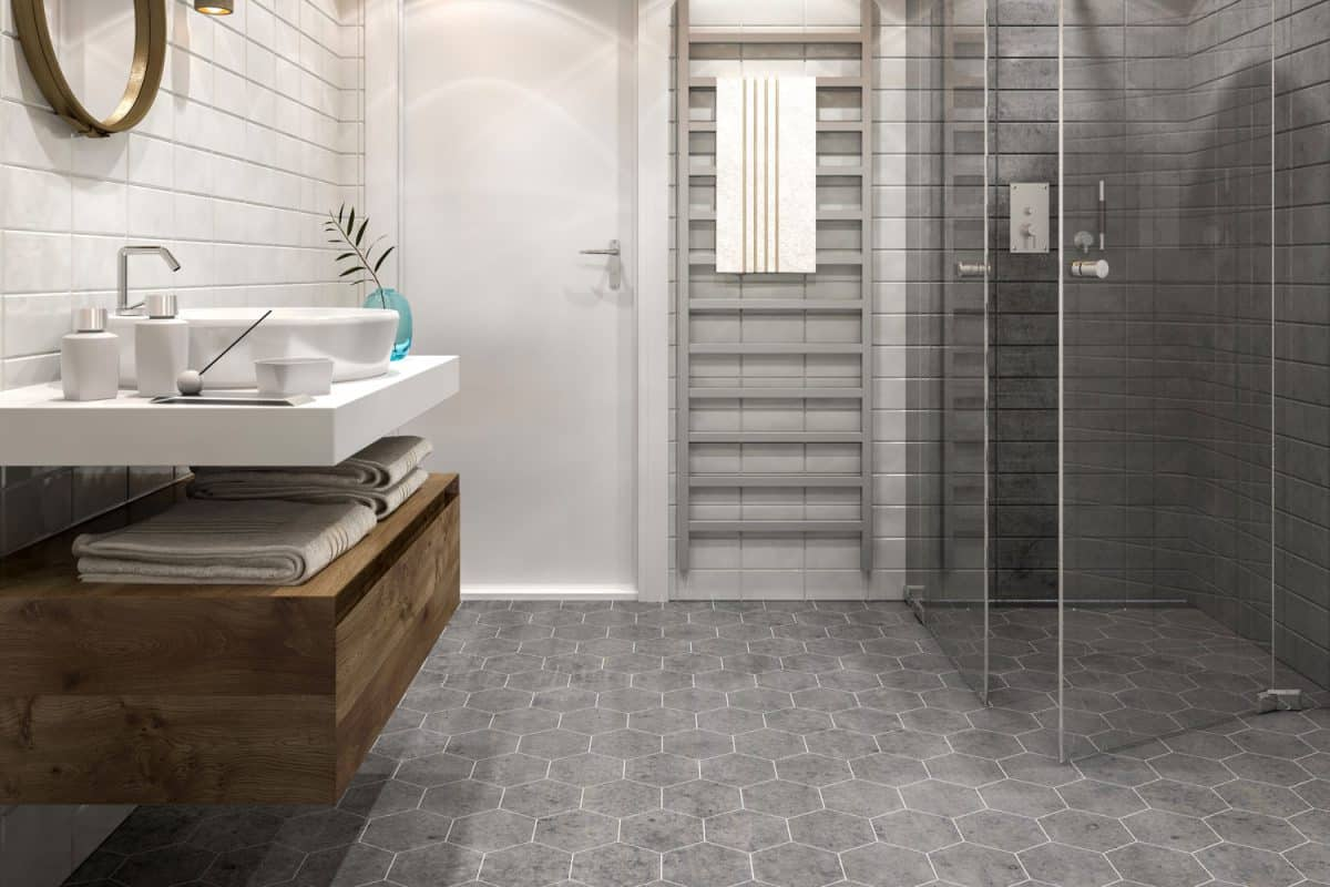 A small modern and luxurious bathroom with hexagonal tiled flooring, glass shower walls, and a rustic vanity