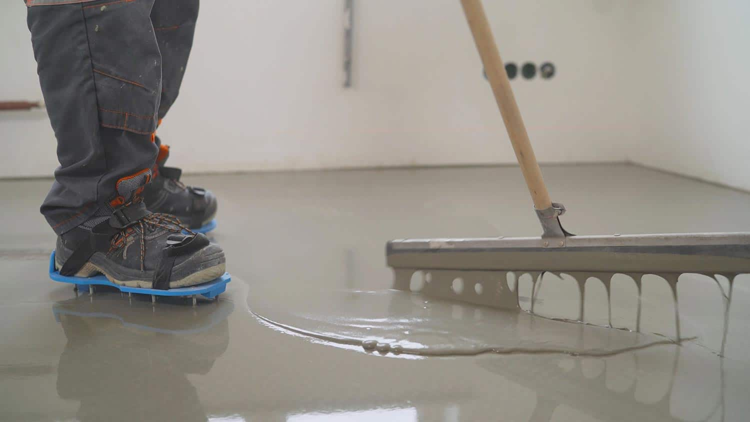 A worker in macro steps applies the solution to the floor