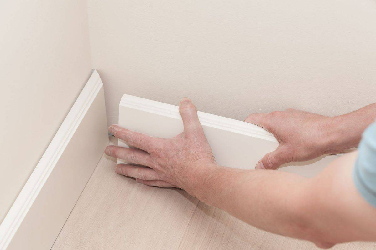 A worker loosening a baseboard to remove a nail