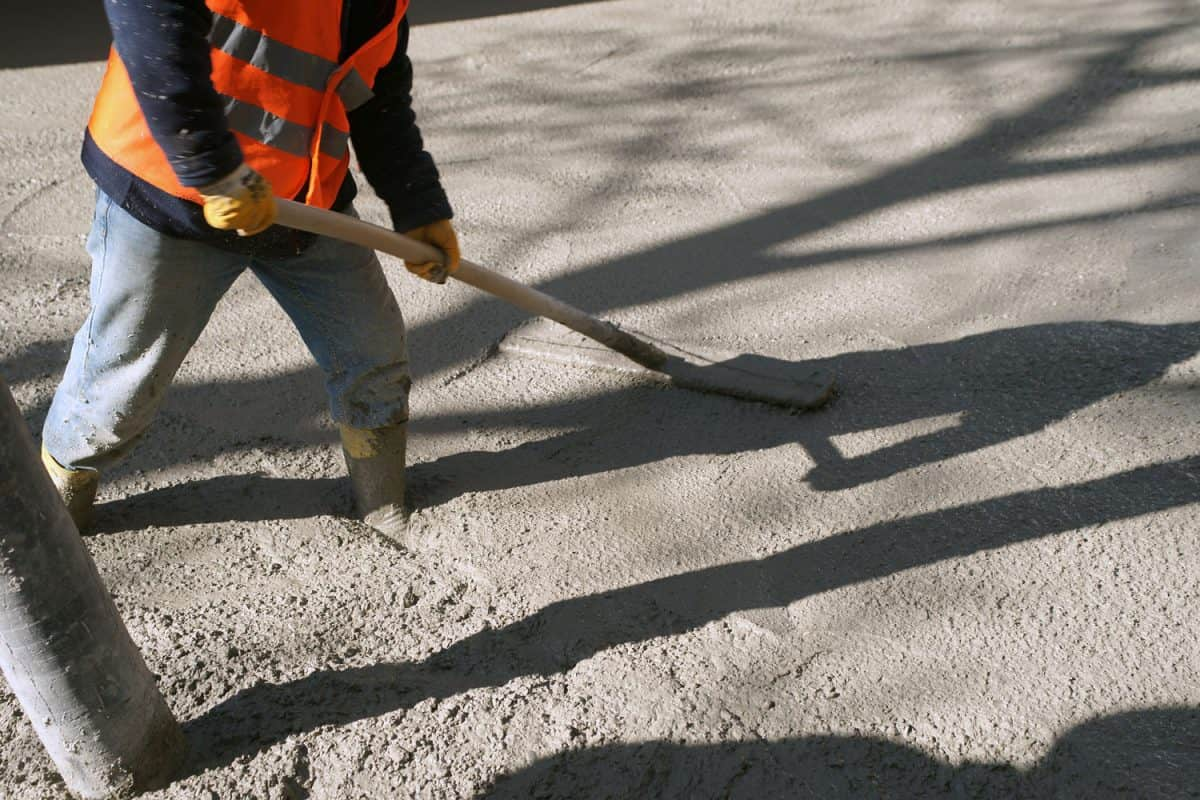 A worker spreading the concrete pour