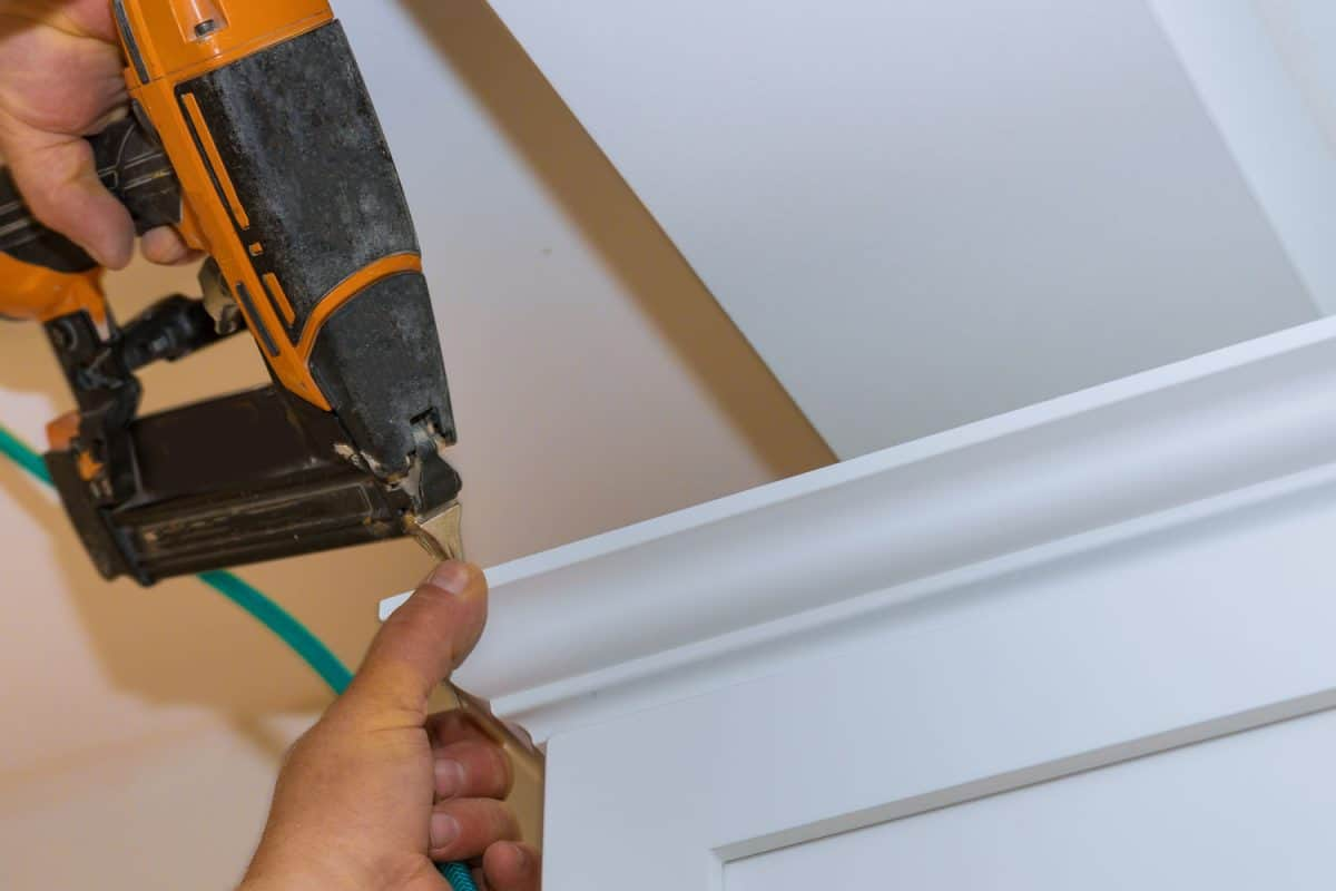 A worker using a nail gun to punch to the ceiling trim