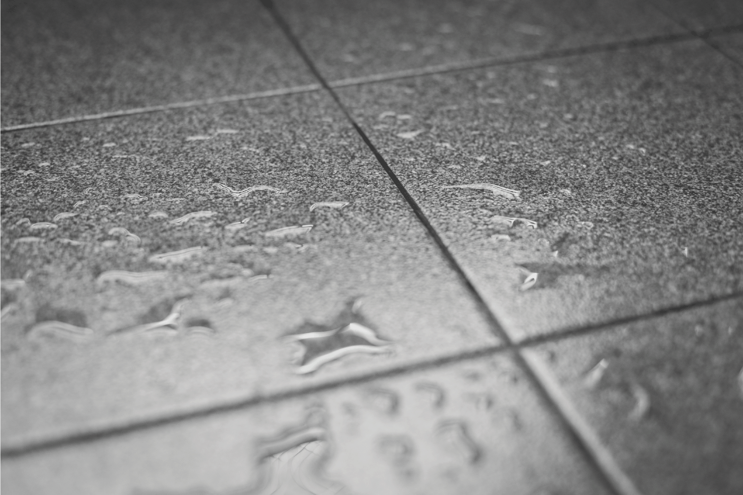 Black and white Selective focus of Water drops on the tile floor texture