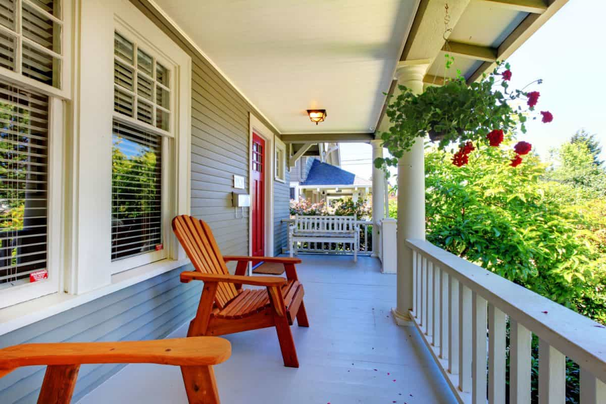 Brightly colored porch with wooden chairs and white painted wooden trims