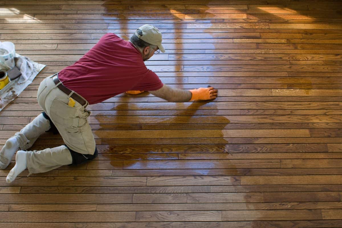 Carpenter staining a hardwood floor. Motion blur on the right hand, How Long Does It Take For Floor Sealant To Dry?