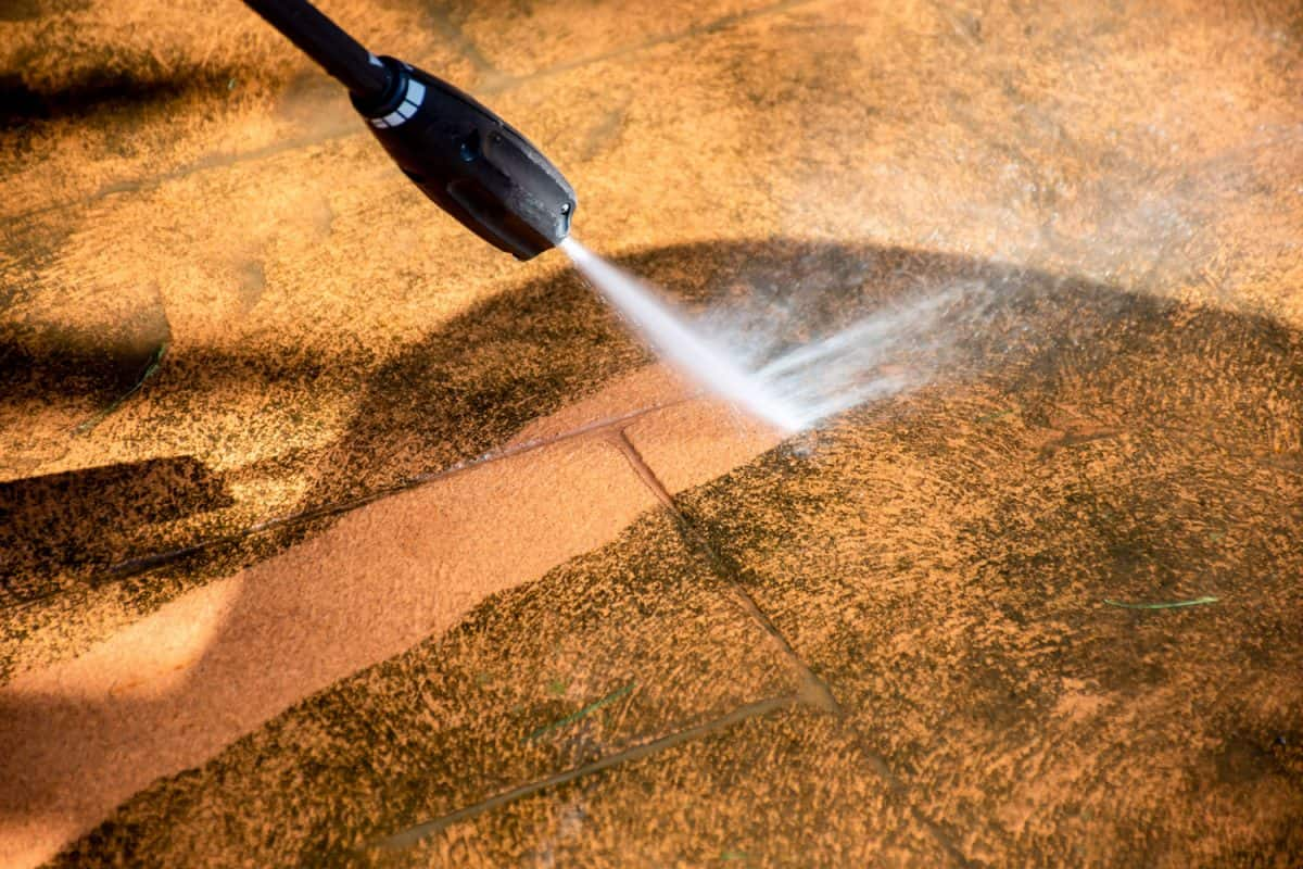 Cleaning backyard paving tiles pathway with high pressure washer
