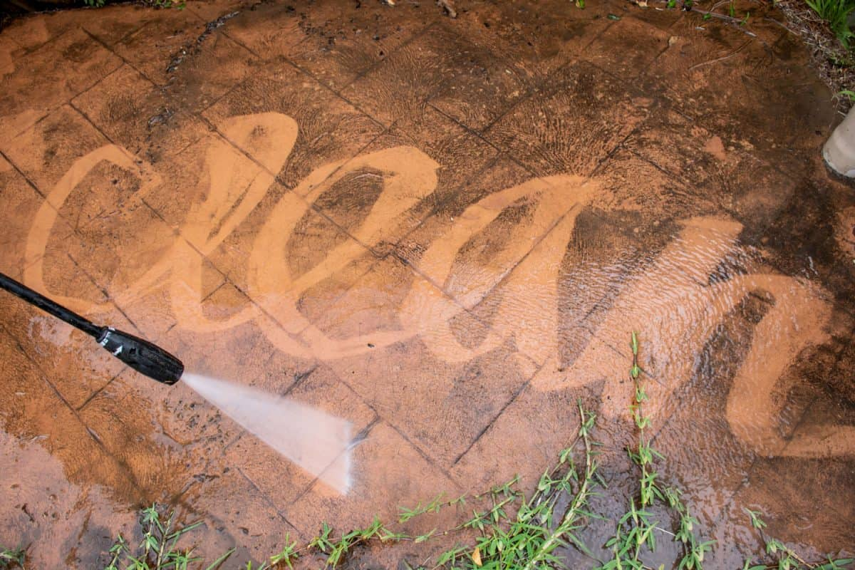 Cleaning backyard paving tiles with pressure washer
