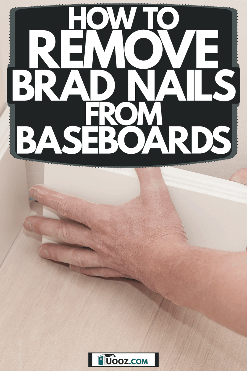 A worker loosening a baseboard to remove a nail, How To Remove Brad Nails From Baseboards