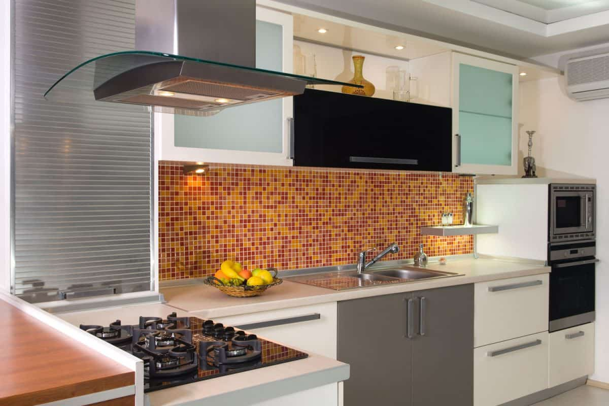 Interior of a gorgeous modern kitchen with a brown backsplash range hood cooktop and white stainless cabinetry