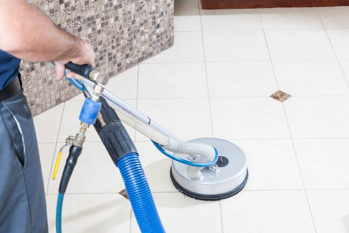 Man cleaning tile and grout with machine in bathroom, 9 Of The Best Floor Grout Cleaner Machines