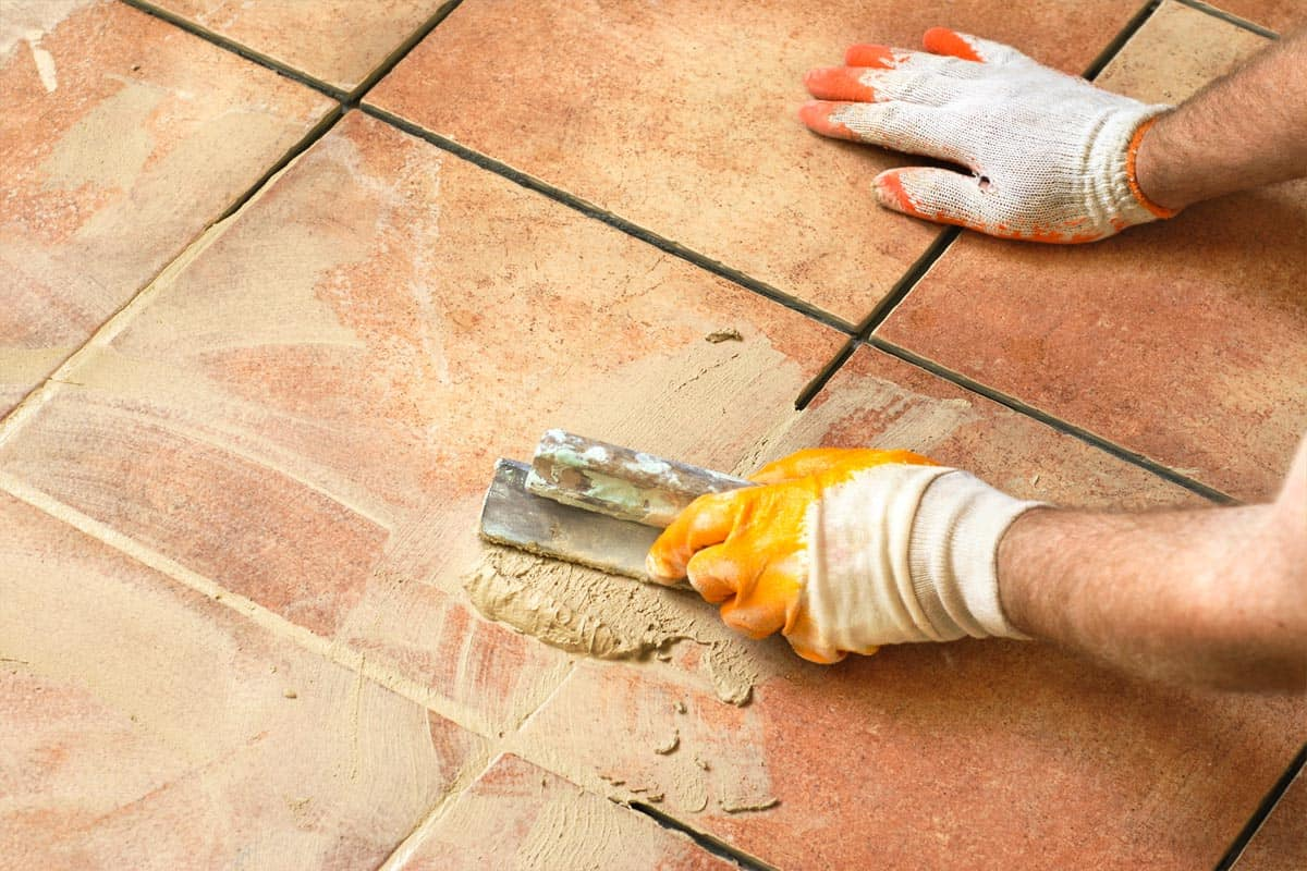 Worker applying tile grout on floor