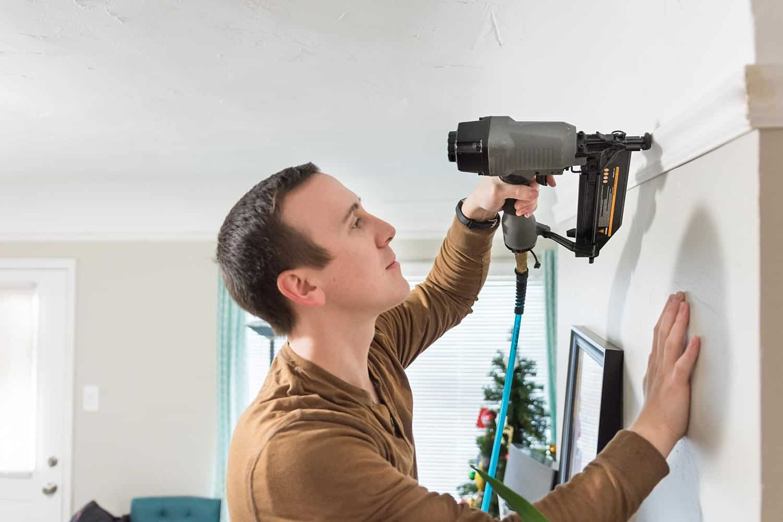 Man using generic nail gun to fasten white trim to wall