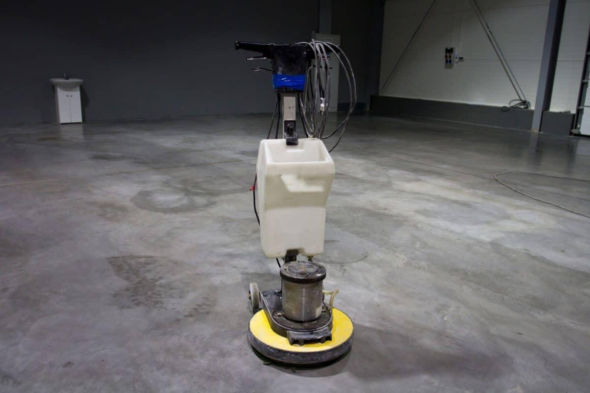 A concrete grinder machine inside an empty living room
