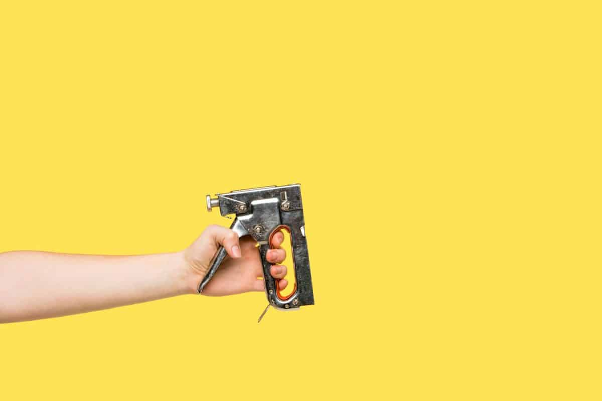 A cropped photograph of a woman holding a staple gun