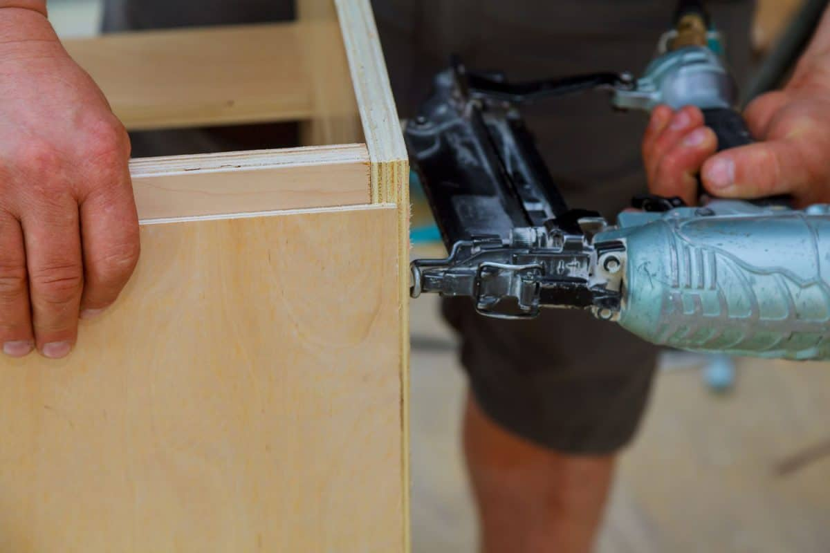 A man using a brad nailer to make a small table using plyboard