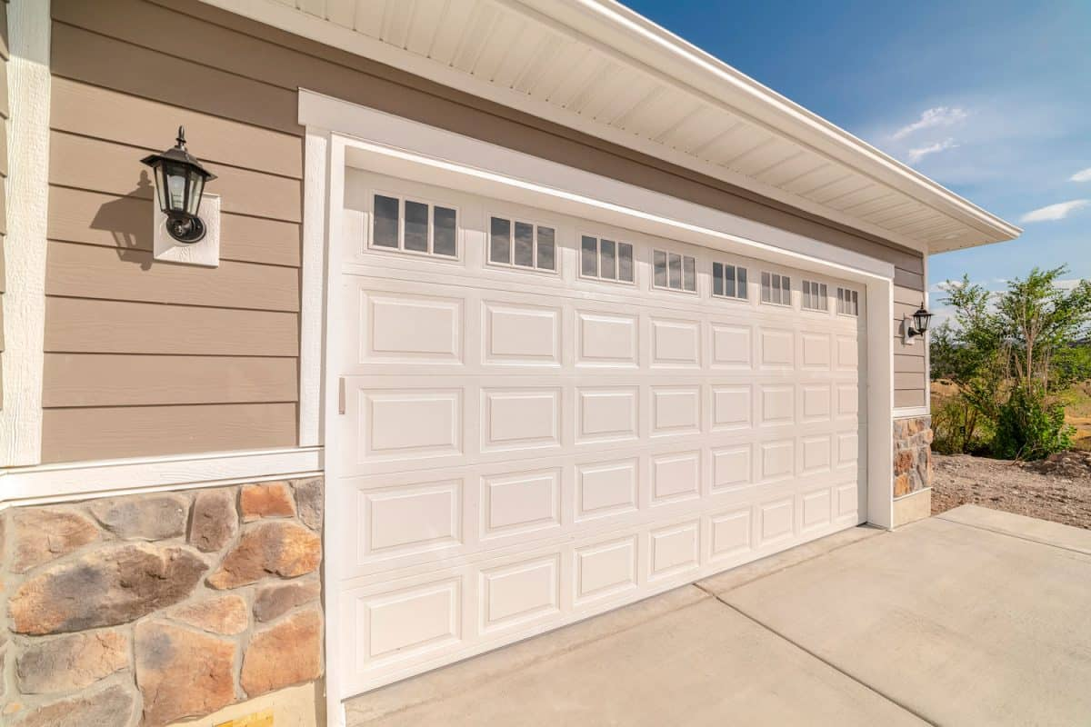 A white long span garage door with small window panes for lighting