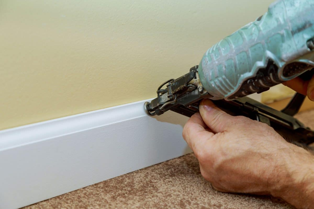 A worker installing a baseboard using a brad nailer
