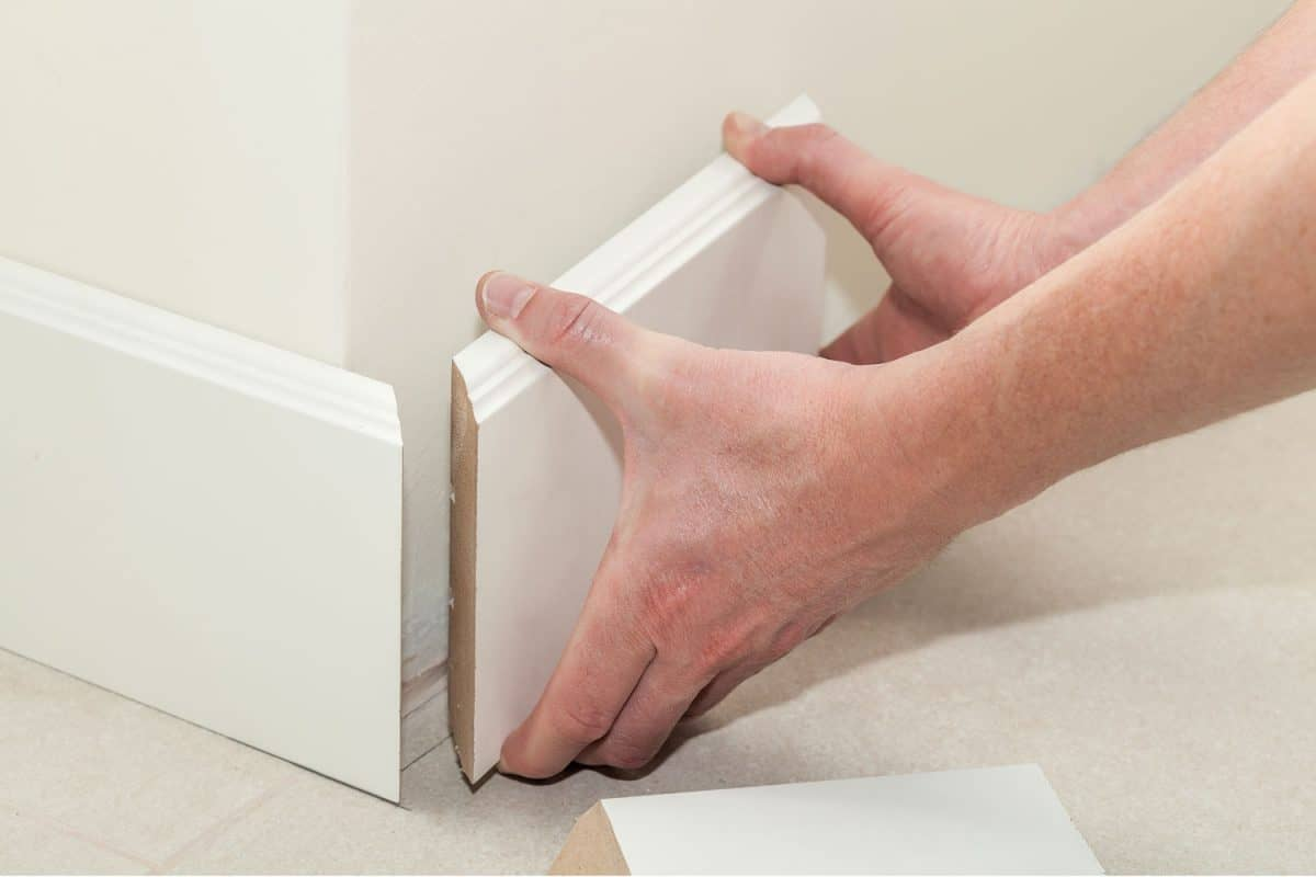 A working lining a baseboard before nailing it
