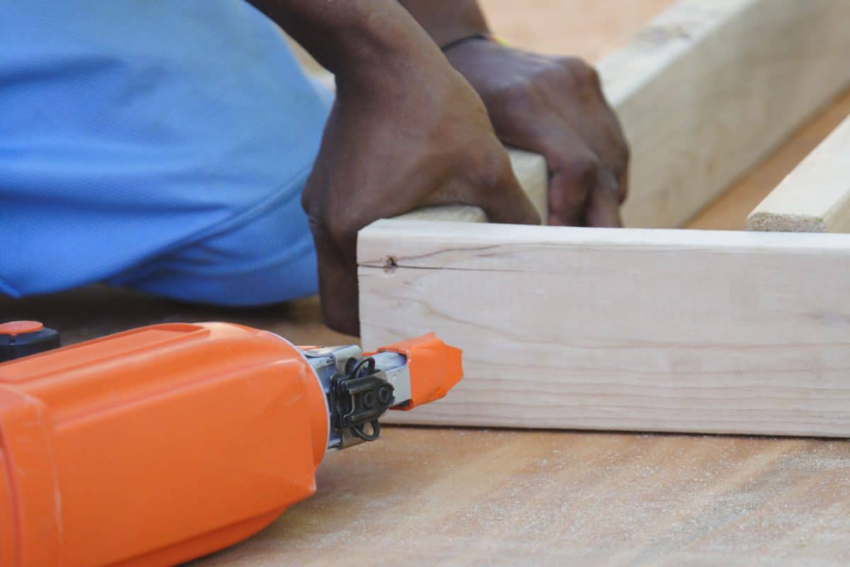 A worker making a window framing using a brad nailer