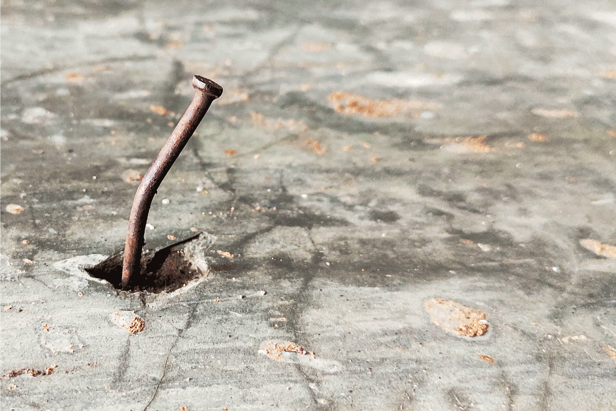 An old rusty bending nail in the concrete. How To Remove Nails From Concrete Floor