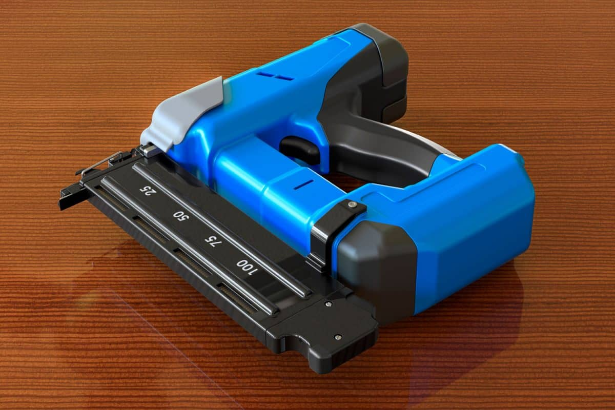 Blue colored brad nailer on a wooden table
