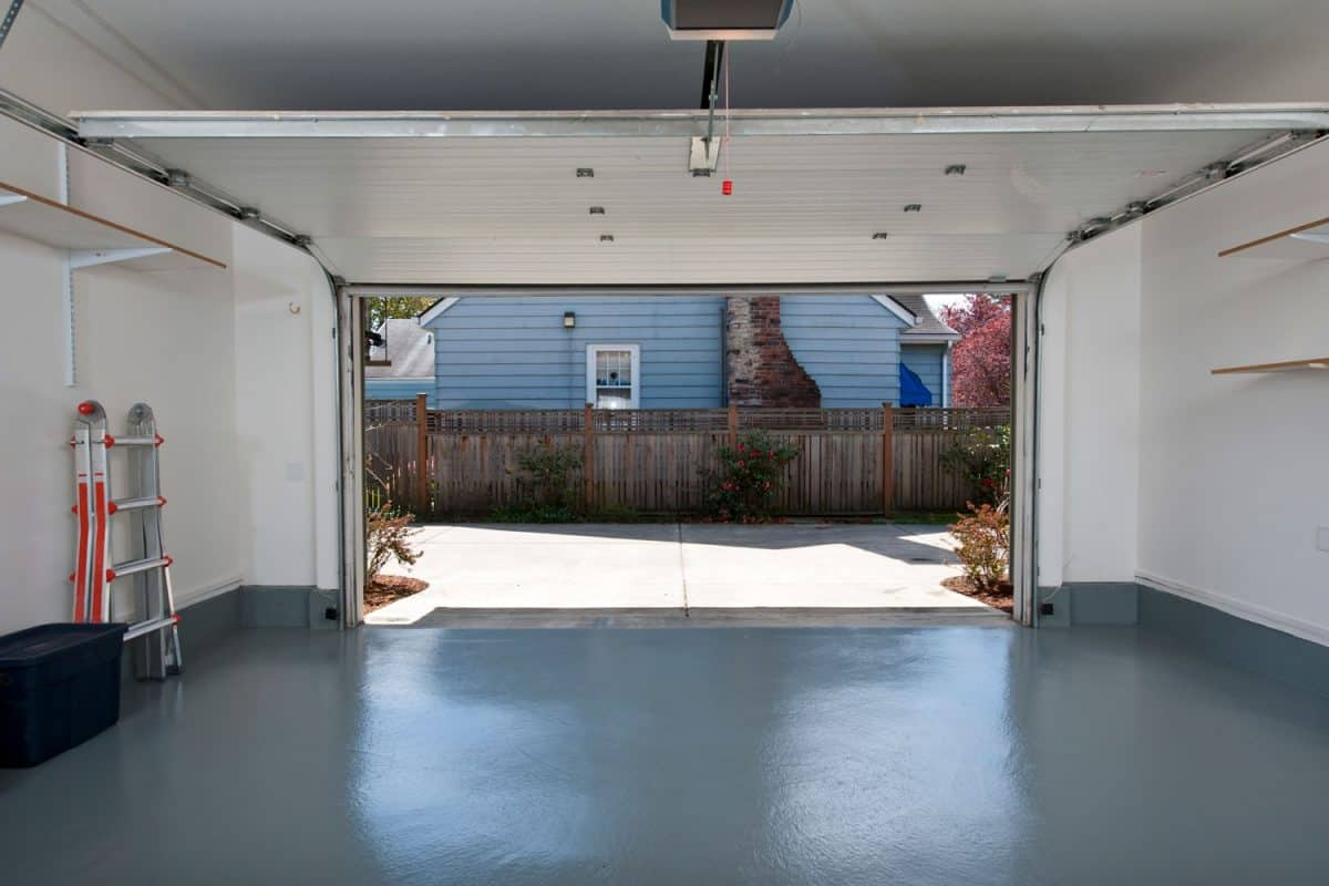 Clean interior of a white wall garage with the garage door opened