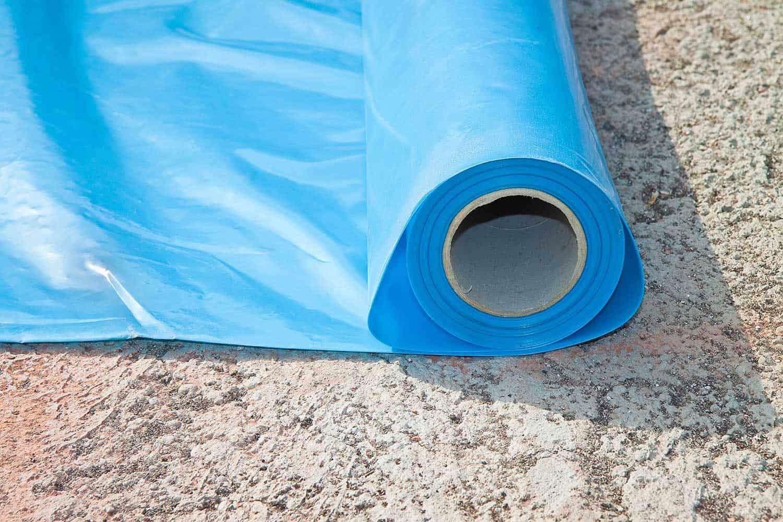 Installing polyethylene protection vapor barrier on concrete floor