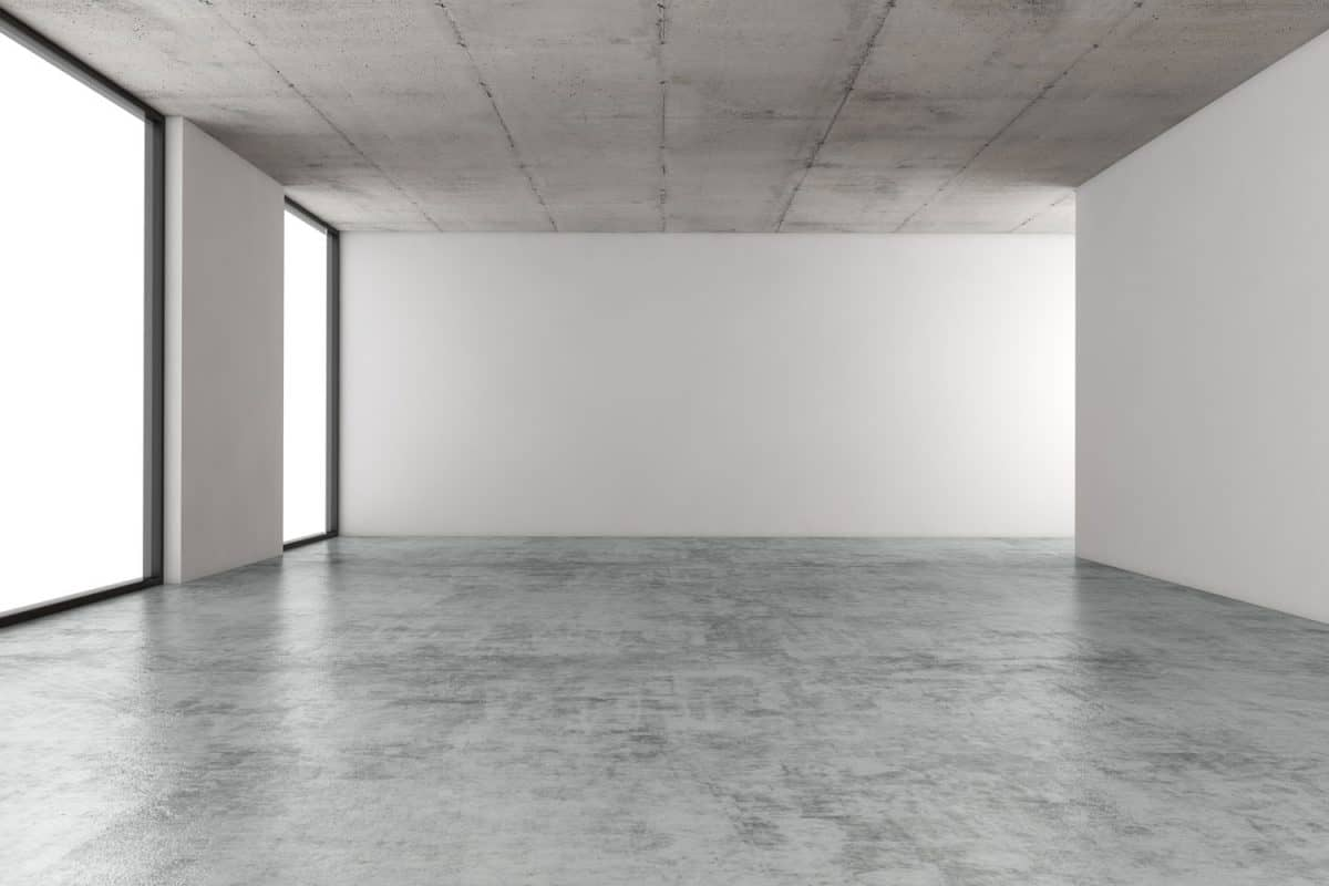 Interior of a huge empty room with concrete flooring huge windows, and gray ceilings