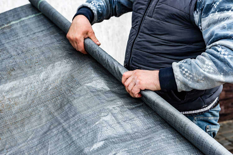 Worker holding roll of vapor barrier membrane for floor
