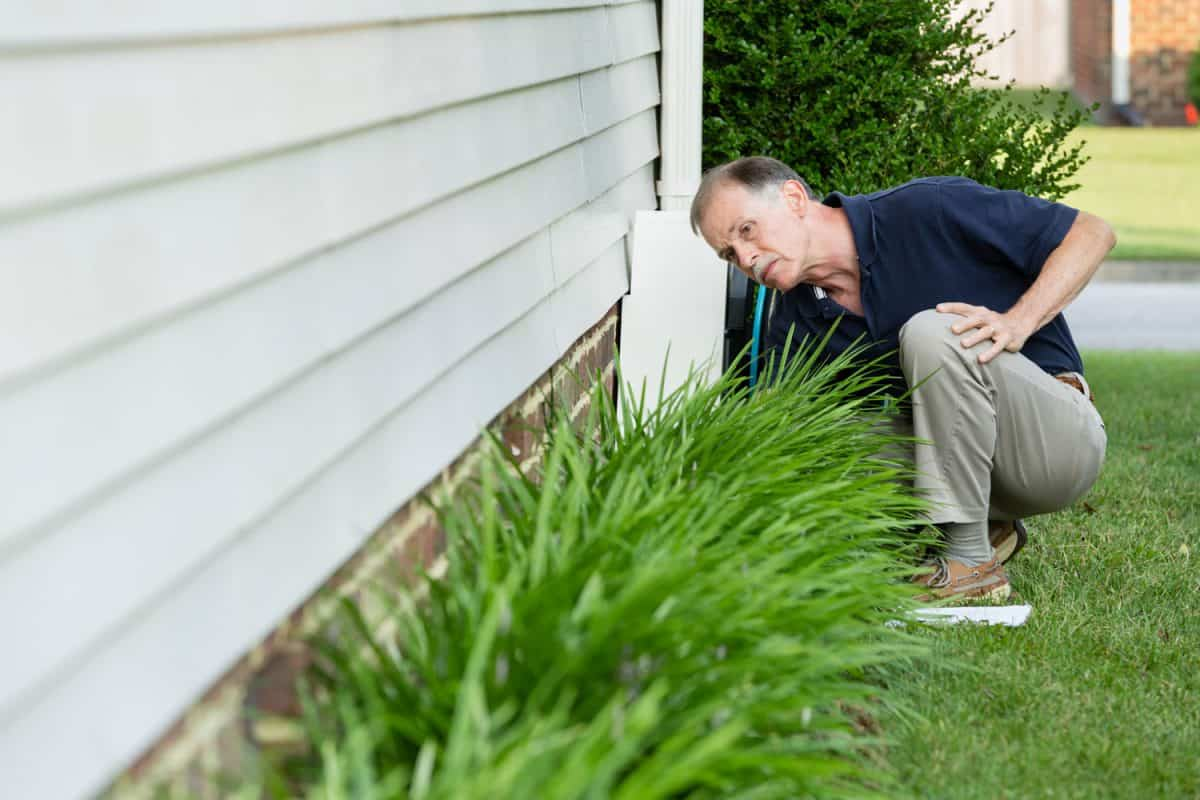 An inspector examines a home's foundation for cracks