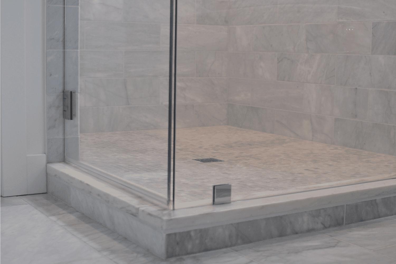 Bathroom shower with glass door and Carrara marble tiles.