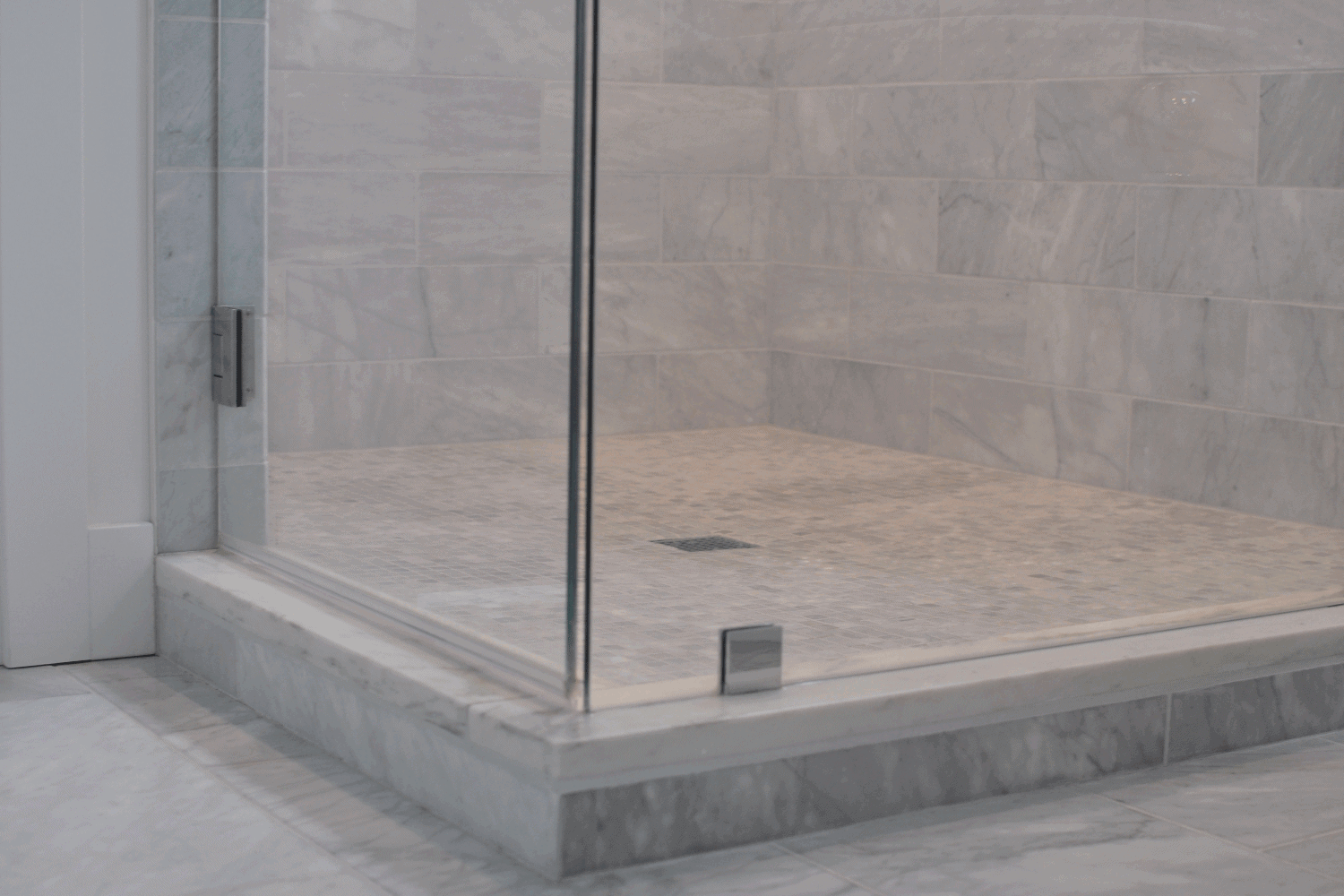 Bathroom shower with glass door and Carrara marble tiles. Should You Tile Under A Shower Base