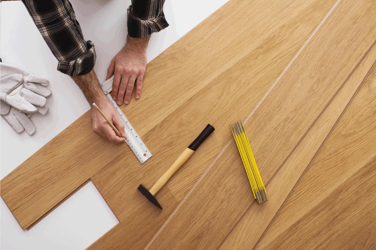 Carpenter installing a wooden flooring. Should You Glue Down Engineered Hardwood Flooring