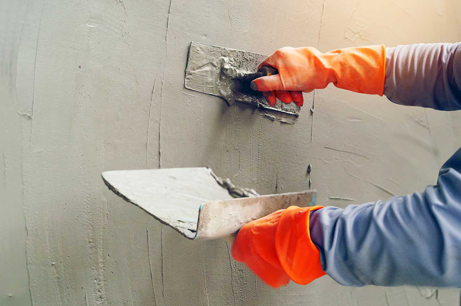Hand of worker with concrete plaster