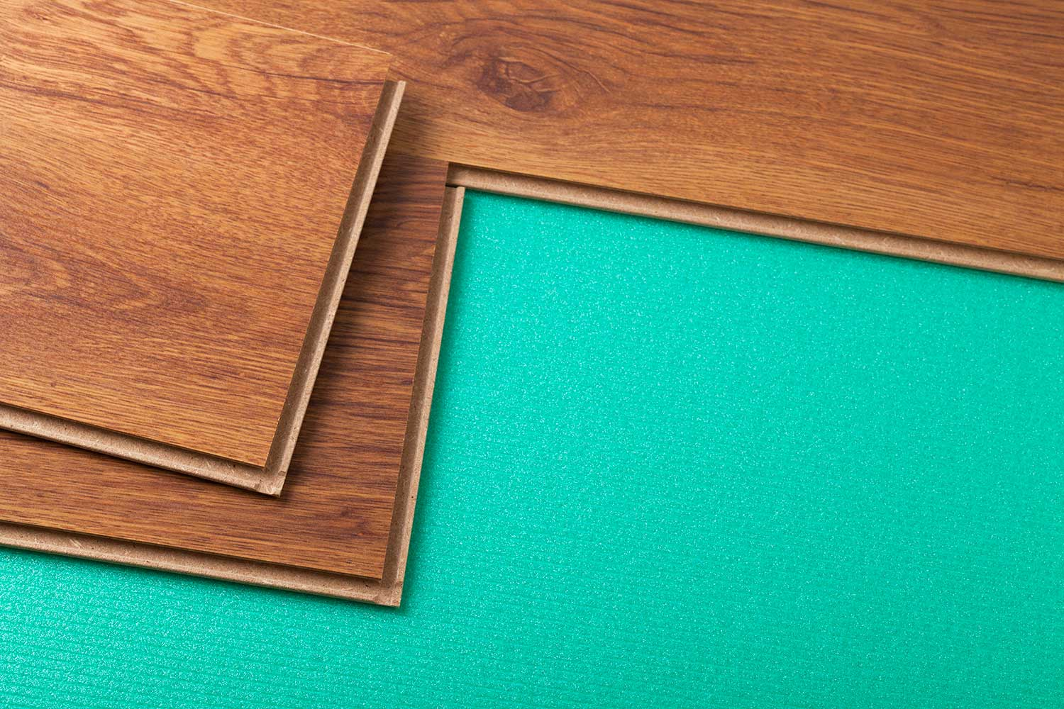 Laying laminate flooring with green foam underlayment