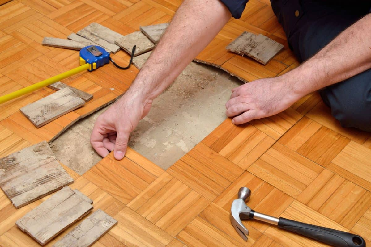 Man removing damaged pieces of wooden flooring, How To Remove Glued Down Wood Flooring