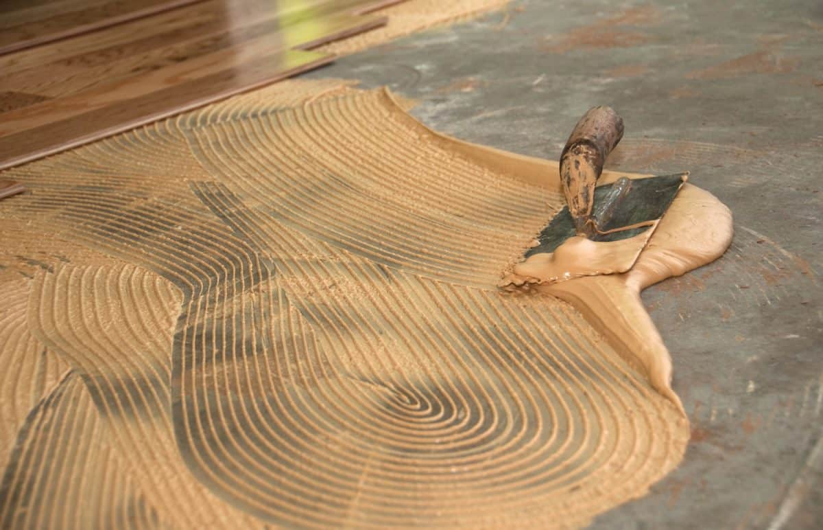 Processing of laying engineered hardwood floor via glue down format. A thin coating of thinset mortar is smeared onto the concrete using a trowel, before the wood pieces are applied.