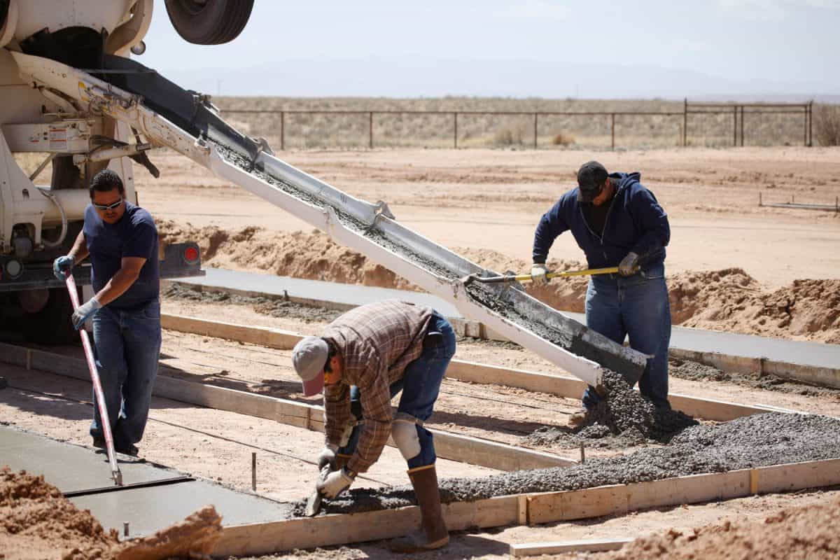 Three men working on a concrete pad for a home foundation